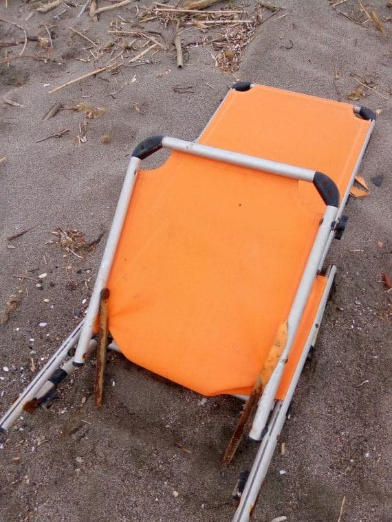 Una tumbona abandonada en la arena.